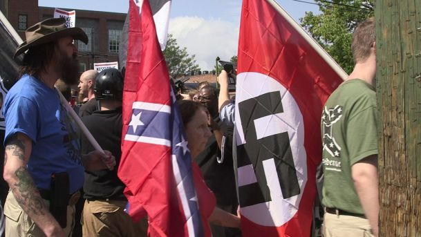 Demonstrators carry confederate and Nazi flags during the Unite the Right free speech rally at Emancipation Park in Charlottesville Virginia USA