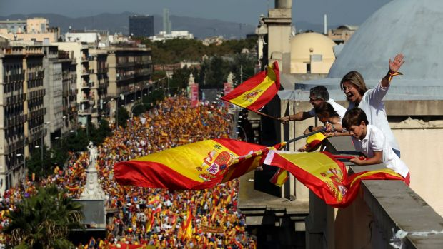 People on a rooftop wave Spanish flags during a march in downtown Barcelona Spain to protest the Catalan government's
