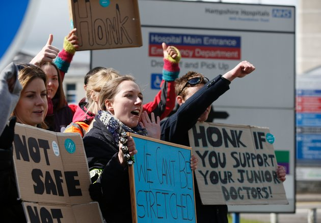 ADRIAN DENNIS via Getty ImagesDemonstrators and Junior doctors hold placards as they protest outside the Basingstoke and North Hampshire Hospital