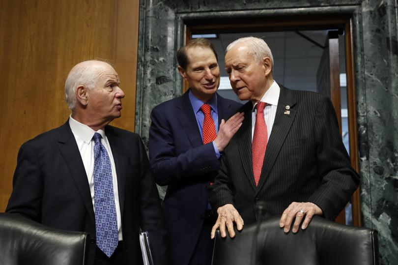 Sen. Ben Cardin D-Md. left talks with Ranking Member Sen. Ron Wyden D-Ore. and Senate Finance Committee Chairman Orrin Hatch R-Utah right at the start of a committee hearing on Thursday Sept. 14 2017 on Capitol Hill in Washington. On Wednesday