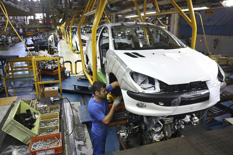 Iranian worker assembles a Peugeot 206 at the state-run Iran Khodro automobile manufacturing plant near Tehran Iran. From brand-new airplanes to oilfields billions of dollars of deals stand on the line for