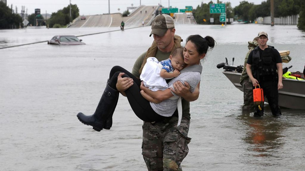 Houston Police SWAT officer Daryl Hudeck carries Catherine Pham and her son Aiden after rescuing them from their home surrounded by floodwaters from Tropical Storm Harvey