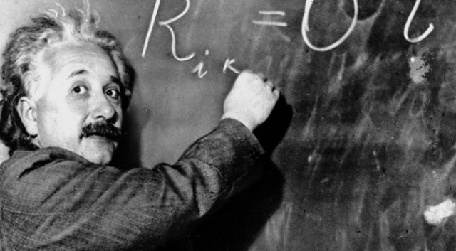 Einstein at a blackboard, writing Rik = O