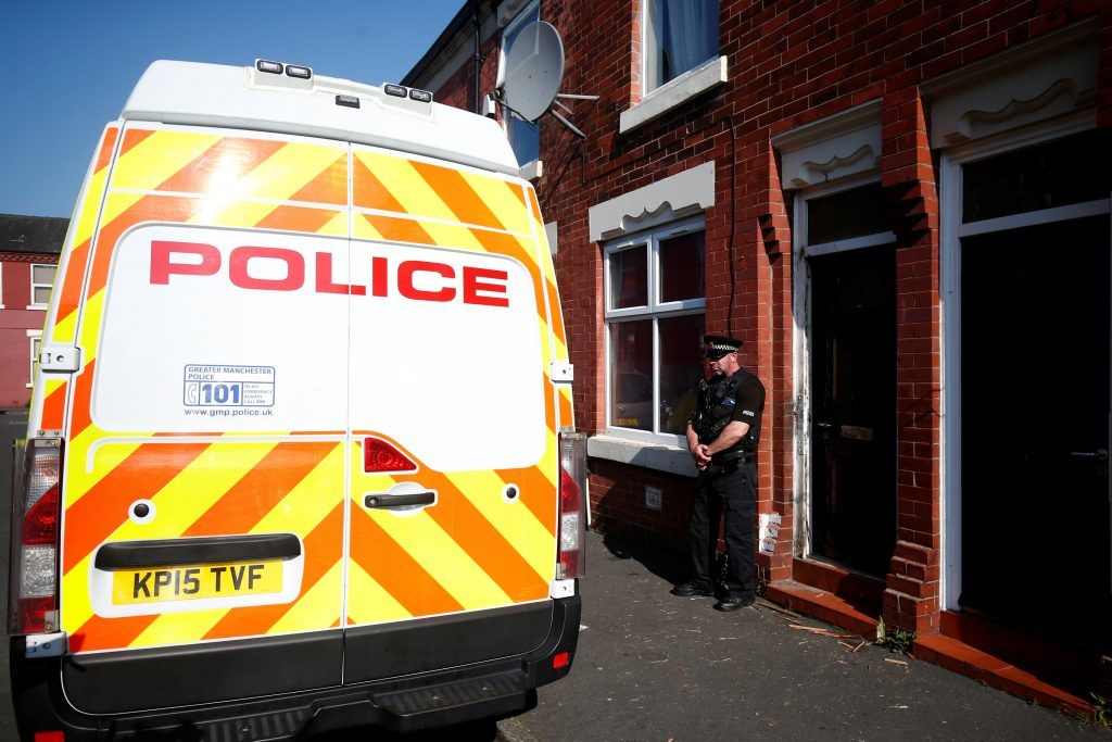 A police officer stand outside a property in Moss Side following overnight raids in Manchester Thursday