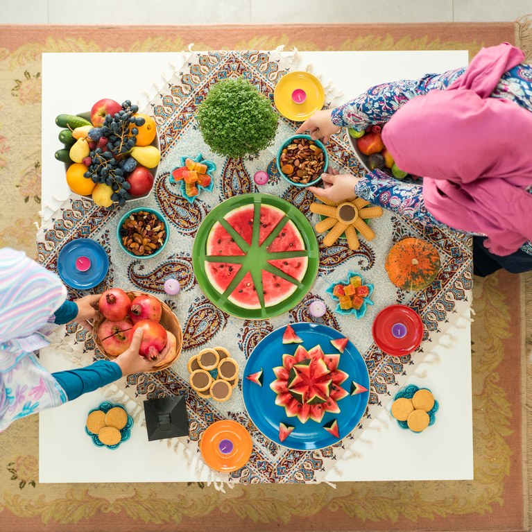 Two females preparing food decorated table ready for family gathering