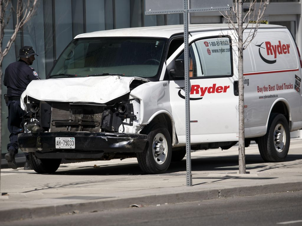 Police inspect a van suspected of being involved in a collision that killed at least nine people and injured 16 others in Toronto on Monday