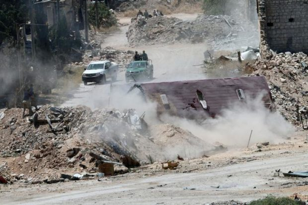 Forces constant to conduct of Syrian regime Bashar al Assad are seen nearby barricades on a Castello highway in Aleppo
