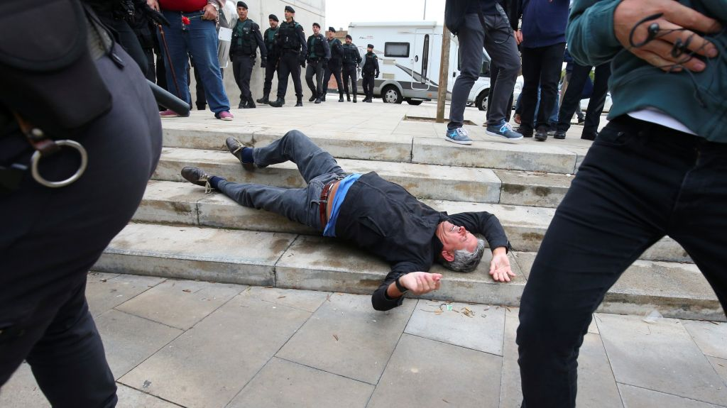A man falls to the ground during scuffles with Spanish police