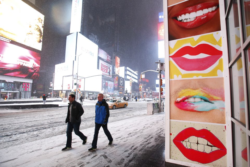 Caption + People walk through New York's Times Square during a snowstorm Tuesday