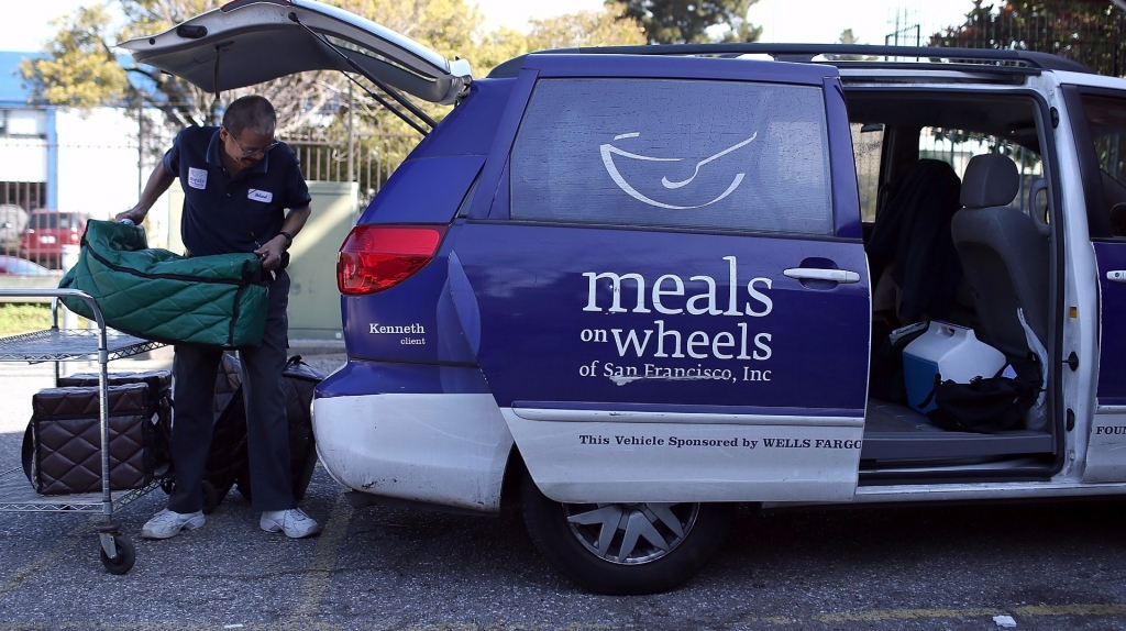 A Meals On Wheels of San Francisco driver loads meals into a van before making deliveries