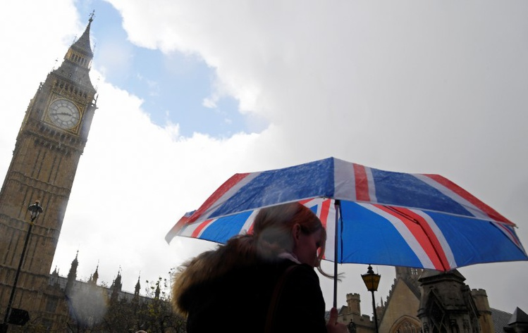 British union flag design umbrella as she walks past the Houses of Parliament in London Britain