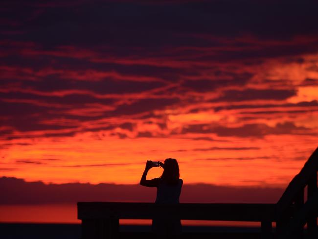 Karen Duer-Potts uses her mobile phone to take a sketch of a nightfall as a outdoor rope of Hermine, that has enervated to a pleasant storm, creeps over a beach during Cape Charles, Virginia. Picture: AP