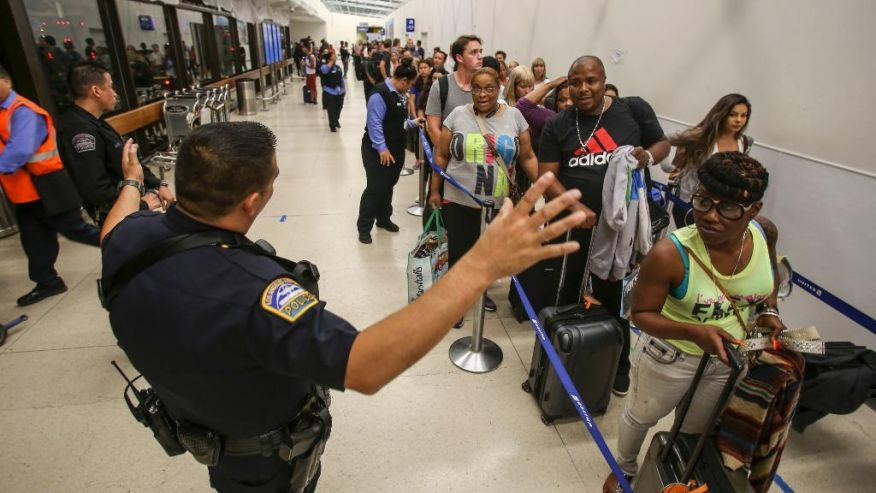 Police officers mount ensure as passengers wait in line during Terminal 7 in Los Angeles International Airport Sunday Aug. 28 2016. Reports of a gunman opening glow that incited out to be fake caused panicked evacuations during Los Angeles International Airport
