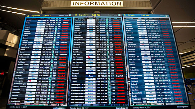 The information board in Terminal C at Logan International Airport shows the majority of flights cancelled