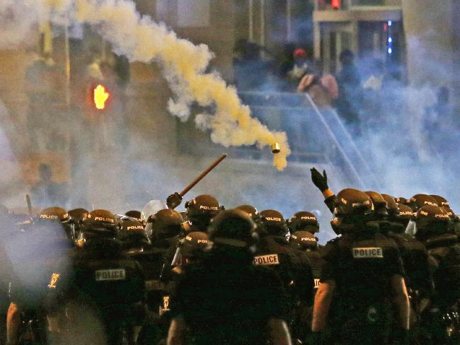 Police glow rip gas as protestors intersect downtown. Picture: AP/Gerry Broome