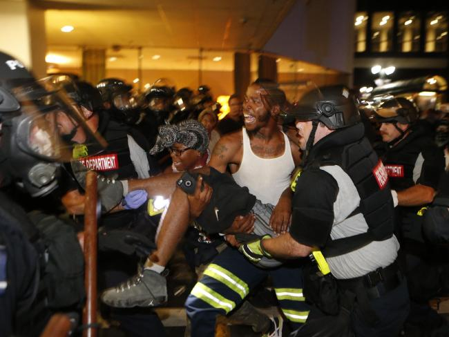 Police and protesters lift a severely bleeding protester. Picture: Brian Blanco/Getty Images/AFP