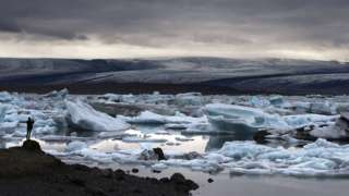A man takes a picture of blue icebergs at the Jokulsarlon glacial lagoon