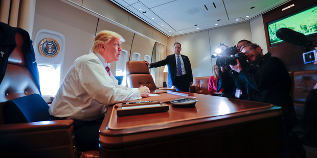 Loading President Donald Trump sits at his desk on Air Force One upon his arrival at Andrews Air Force Base