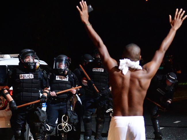 A male raises his arms in front of officers in Charlotte after a night of aroused protests. Picture: Jeff Siner/The Charlotte Observer around AP