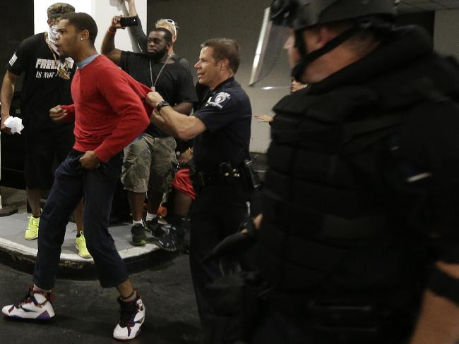 A male is incarcerated by military during a aroused protests that saw protesters rush military in proof rigging during a downtown Charlotte hotel. Picture: AP/Chuck Burton
